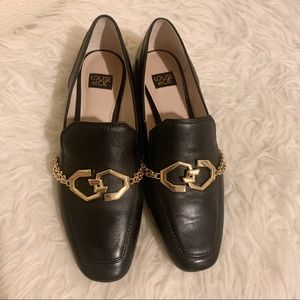 Black Leather Loafers With Gold Chain Detail.